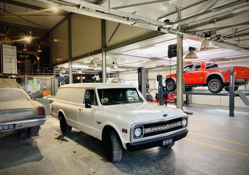 Oude Chevrolet Suburban in de garage voor APK